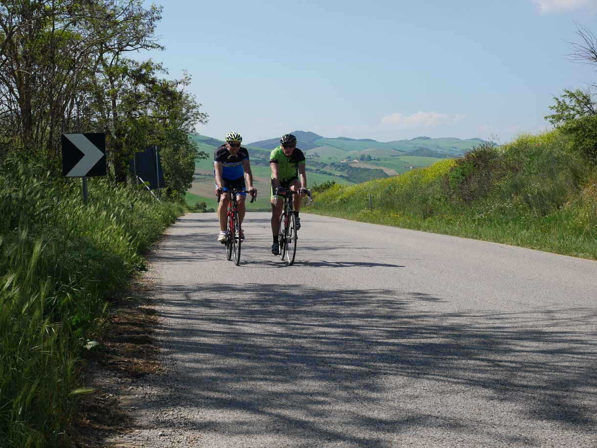 Two british cyclists accross one of the provincial streets in Basilicata